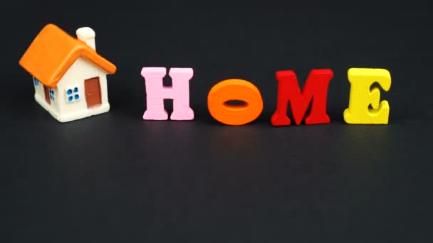 Real estate concept. Decorative letters forming word HOME with house on black background
