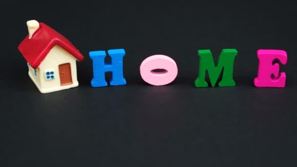 Barevná písmena izolovaná na černé: HOME