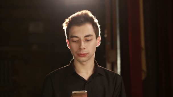 Portrait of man against backlight background who is typing text message by smart phone