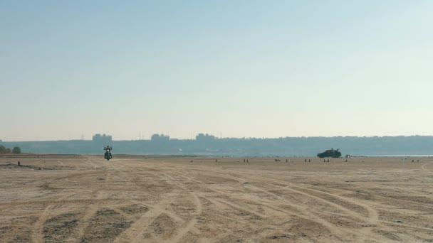Motorkář na koni podél písečné pláže. Motocyklista jezdí na motocyklu přes poušť.