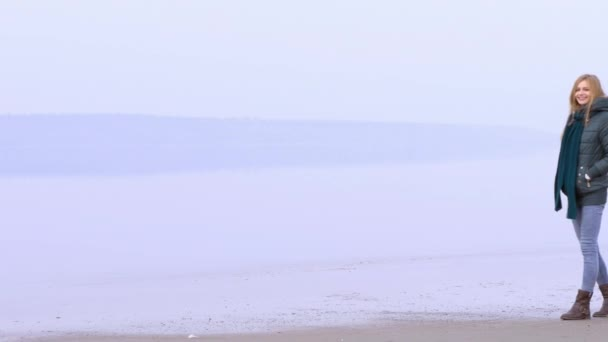 Young beautiful girl walking on the sandy beach and smiling.
