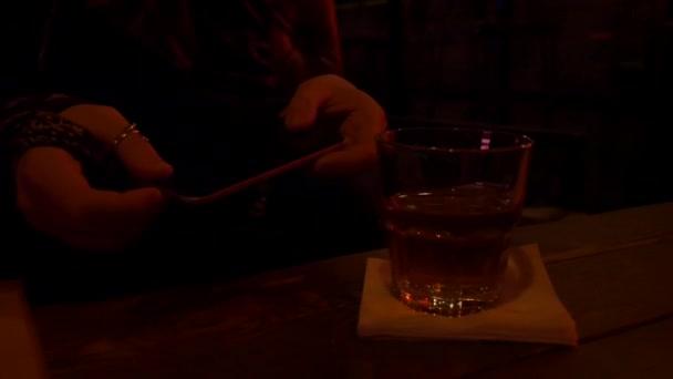 Ženské ruce s mobilním telefonem v nočním klubu.