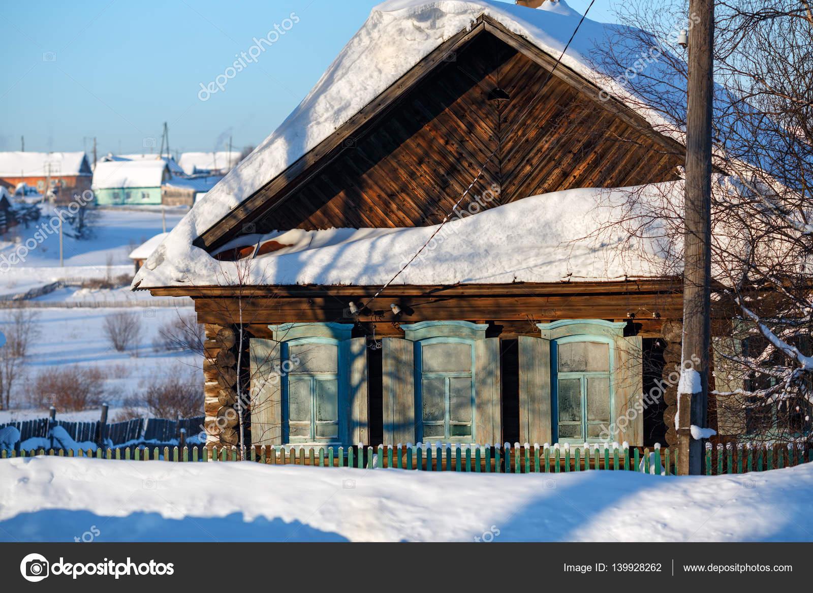 Russische Blockhäuser das verschneite alte blockhaus mit hölzernen fensterläden dorf