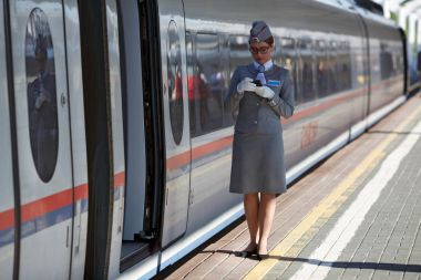 The train conductor waiting for the passengers of the high speed electric train Sapsan between Moscow and Saint Petersburg. Moscow, Russia