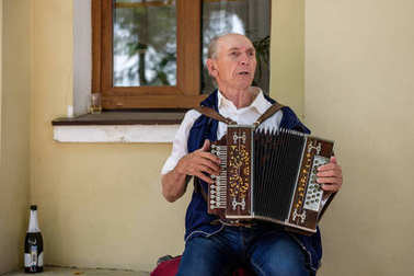 An elderly man playing the russian accordion in front of the registry office. Suzdal, Russia.