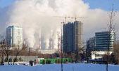 Fotografie Wohnhaus im Bau auf dem Hintergrund der rauchenden Schornsteine der Kraft-Wärme-Kopplungsanlage. Moskau, Russland