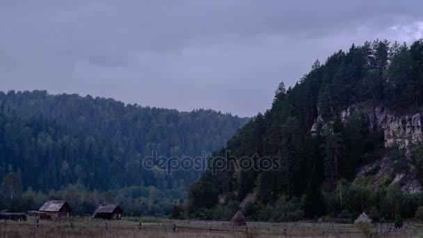 Vesnice v horském lese. Za soumraku. Idylický. Domy na okraji obce. Stoh sena