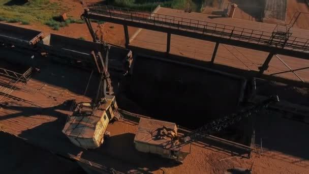 Drcení a třídění rostlin. Zpracování nerostných surovin. Rypadlo se uvolní rudy z auta. Panorama. Pohled shora. DRONY