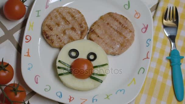 Kreativní zábava jídlo pro děti - myš ústí dva kuřecí steaky a bramborovou kaší ve tvaru kulaté v bílé deska deska s malované dopisy