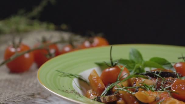 Penne těstoviny s cherry rajčátky, lilek, zdobené Ostravu s bazalkových listů v hluboký talíř se zeleným okrajem. Detail. Zpomalený pohyb