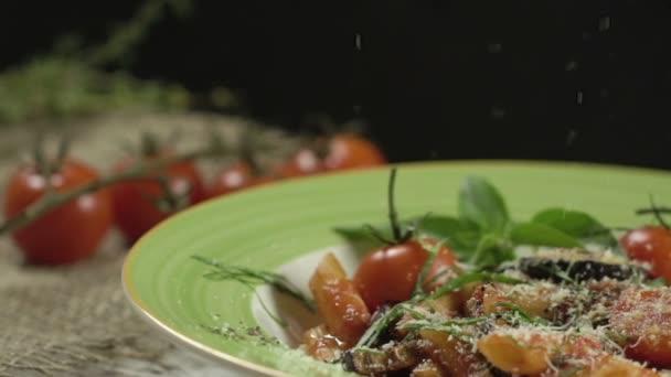 Klesající sýr na penne těstoviny s cherry rajčátky, lilek, zdobené Ostravu s bazalkových listů v hluboký talíř se zeleným okrajem. Detail. Zpomalený pohyb