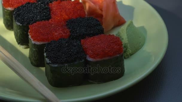 Cheess Square sushi tekercs lazac, uborka, krémsajt, piros és fekete Tobiko, nori, sushi-rizs. Lemez. Pálcika, marinált gyömbér és Wasabi. Közeli.