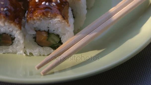 Étvágygerjesztő csodálatos Dragon négyzet sushi tekercs, angolna, lazac, uborka, nori, sushi rizs, szezámmag. Lemez. Pálcika, pácolt gyömbér és a wasabi. Közeli kép:.
