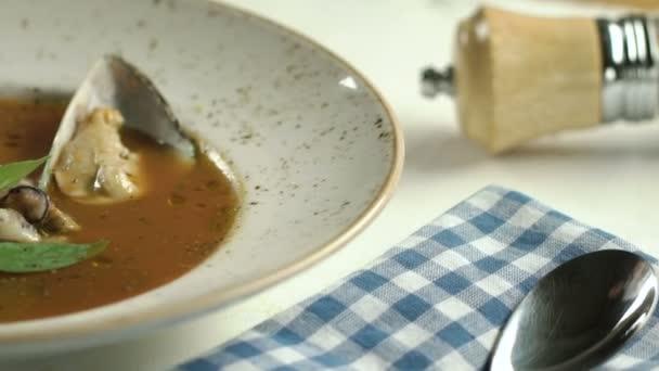 Rajčatová polévka s mořskými plody s listy bazalky a cherry rajčátky na bílé plotně na stole. Ruční přidá ústřice. Zpomalený pohyb.