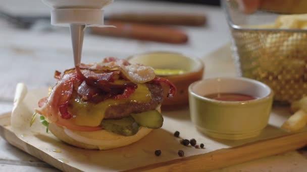 Populární fastfood: měkké hamburger s čerstvým masem. Kuchař nalévá kečup. Zpomalený pohyb