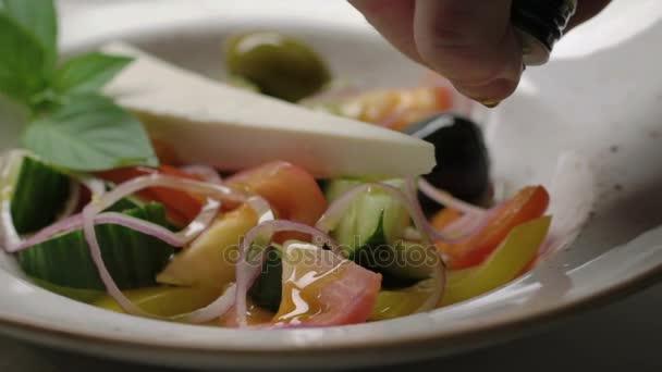 Řecký salát okurky, rajčata, paprika, olivy a sýr je oblečená s olivovým olejem. Zpomalený pohyb
