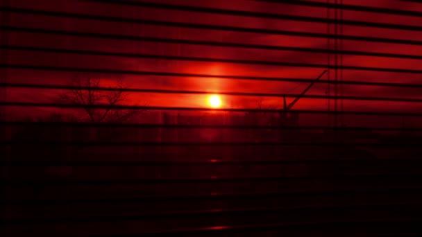 Pohled z okna kanceláře přes žaluzie průmyslové oblasti v době zanikla crimson sunset