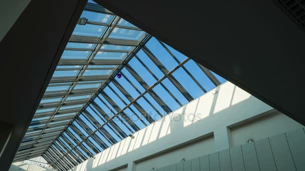 Glass ceiling of the shopping center with paper garlands on a background of time-lapse light of the sun rays on a blue sky