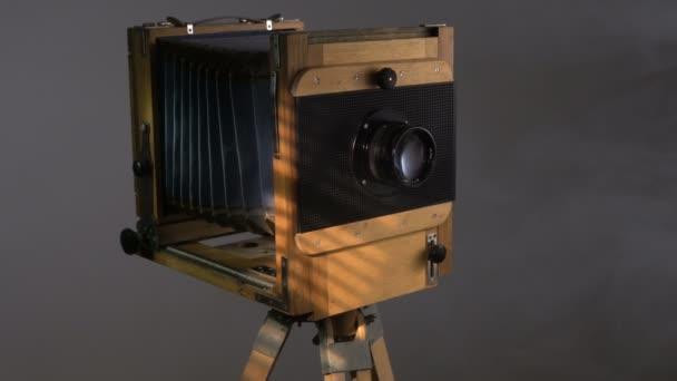 Követés serpenyőben közepes lövés a régi vintage fából készült fénykép fényképezőgép világítás a napfény segítségével a vakok a szürke háttér.