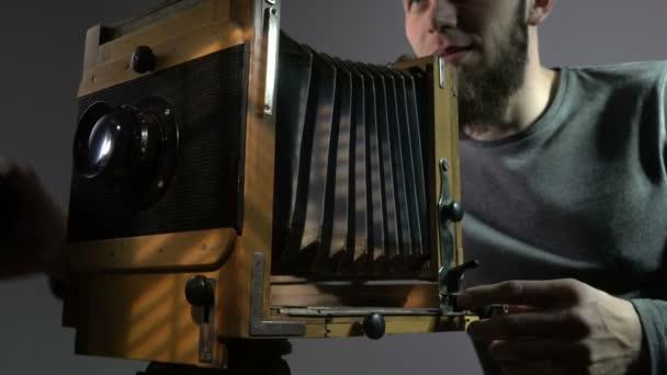 Alacsony, szög, kilátás a szakállas fotós régi vintage fából készült fotó kamera és a bevétel-kép.