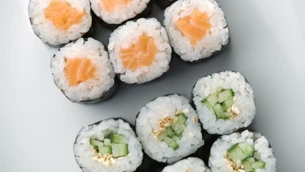 Sada čerstvých sushi rolí se otáčí. Typické japonské jídlo, pokrm z rýže, avokáda, lososa, tuňáka, krevet, sóji, ryb, kaviáru. Japonská restaurace menu, Kalifornie set. Pohled shora, pohled shora, pomalé