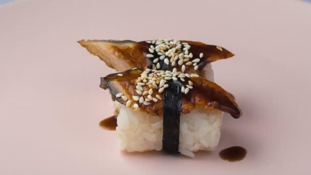 Két angolna nigiri sushi forog a rózsaszín tányéron..
