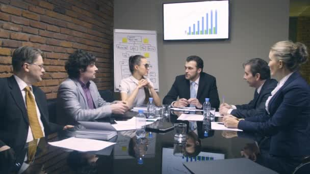 Cheerful businessman speaking with colleagues in meeting room