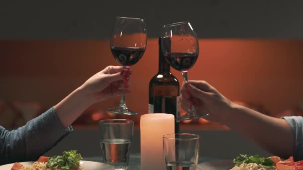 Man and woman clinking glasses with red wine