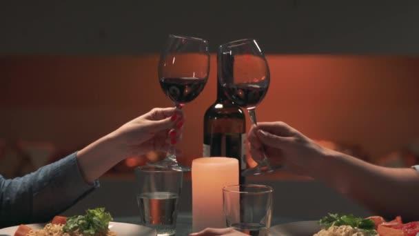 Muž a žena řinčí poháry s červeným vínem