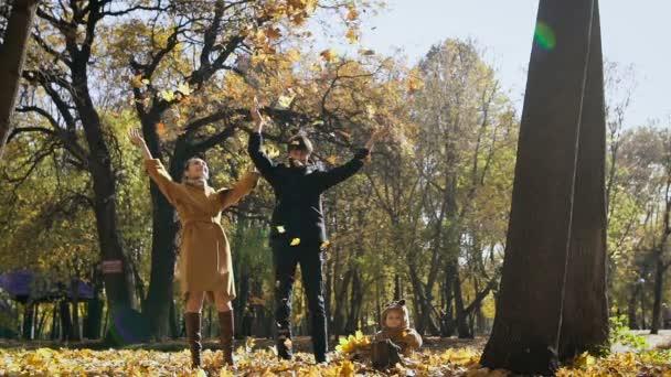 Boldog család játszik az őszi levelek parkban. Anya és apa hányni bérelhet a levegőben. Kis gyerek pillantást nekik, és birtoklás móka.