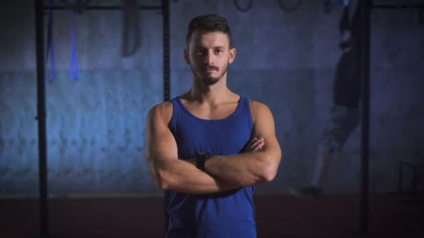 Strong man in blue shirt with arms crossed posing at the gym.