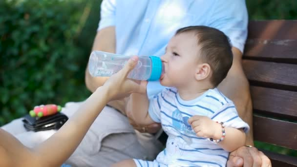 Mom keeps a bottle of water, when the child is drinking.