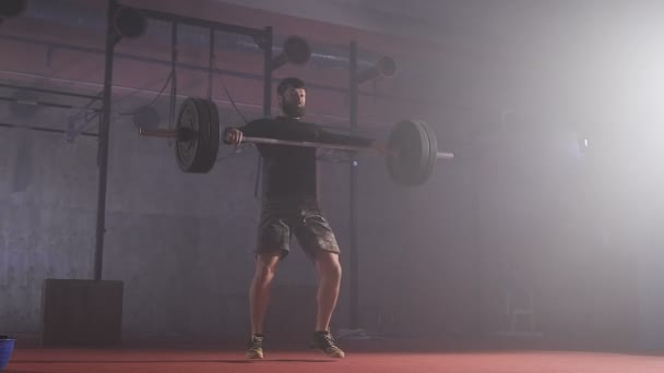Strong man doing barbell snatch exercise at the gym in slow motion.