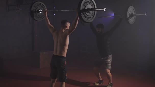 Two strong men doing weightlifting with barbell at the gym simultaniously.
