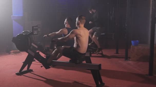 Side view of sportsmen doing rowing and cycling exercises at the gym.
