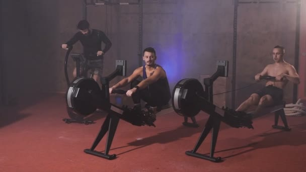 Front view of sportsmen doing cycling and rowing training at the gym.