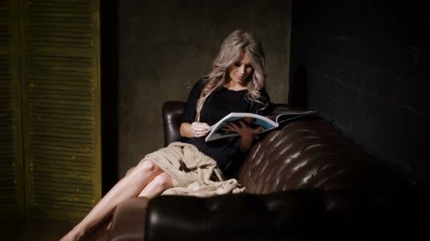 Těhotná žena v krásné černé šaty sedí v temné místnosti na velké hnědé kožené pohovce s růžový pléd na kolena a obracet stránky časopisu