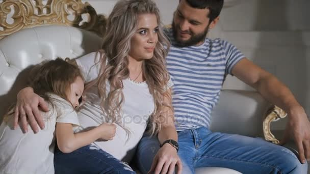 Father, pregnant mother and little daughter are together lying on the couch and hugging each other. Daughter is playing with mothers hair, embracing her and stroking her belly.