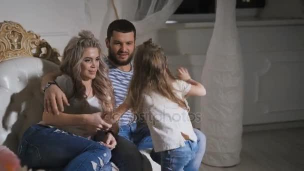 Otec, matka a dcera malá jsou šťastná rodina očekává narození dítěte. Tři šťastní lidé sedí spolu na pohovce, objímaly a usmívá se