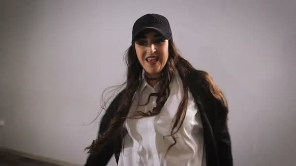 Zblízka happy dlouhovlasý mladé ženy v bílé košili, černé kalhoty, bundu a černou čepici skákání a ukazuje moderní jazzový tanec