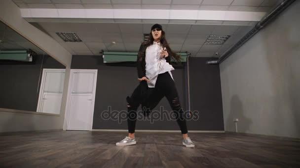 junges Mädchen, das modernen Tanz in schwarzen Kleidern tanzt. Tänzerin macht während ihres Tanzes eine schnelle und aktive Bewegung von Armen und Beinen.
