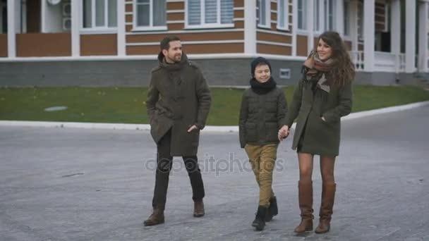 Mladá rodina v teplé oblečení jsou společně chůzi na ulici se smáli a povídali. Otec a matka šťastně hledají k sobě a jejich syn