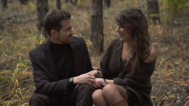 Married couple. Stunning forest. Couple spends his weekends in the woods. They sit on a wooden stump in the woods. Lovers of sweet talk to each other. Beautiful weather sets them on a pleasant chat