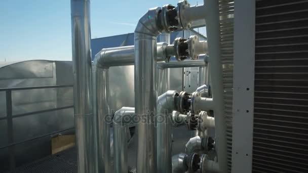 Chrommetallrohre sind an ein gemeinsames Wasserversorgungssystem für das Unternehmen angeschlossen. auf dem Dach eines Industriegebäudes verfügt über eine Menge Ausrüstung, die für die Wartung der Anlage notwendig ist.