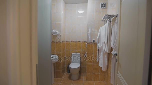 Badezimmer mit Waschbecken, WC, Spiegel und weiße Handtücher und ...