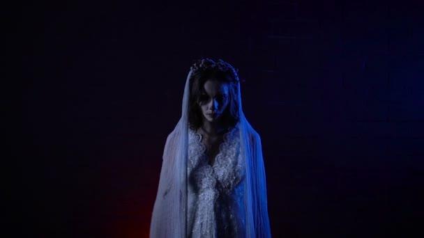 Nahaufnahme einer gruseligen Szene mit Phantom einer Braut gekleidet in weißem Kleid und Schleier, die stehen und starrte auf die Kamera. Junger Geist der Braut steigt ihre Hände zweimal wie Flügel