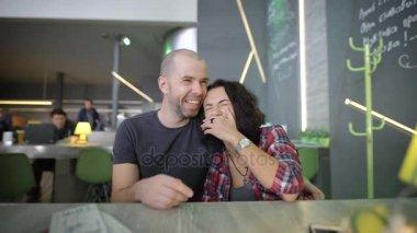 Mladá černovlasá dívka oblečená v červené košili a vousatý muž v šedé tričko, sedí blízko sebe v kavárně u stolu, smáli se, žertuje, drží že navzájem ruce a těší