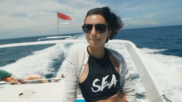 Zblízka atraktivní mladá brunetka v černé tílko a bílé sako si užívat své dovolené na palubě jachty v oceánu. Šťastná dívka v sluneční brýle potěší s větrem, se její tvář