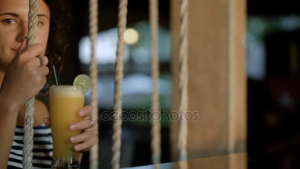 Attraktive lächelnde Brünette spielt abends auf Schaukel mit Cocktail in der Hand. Junges schönes Mädchen trinken Erfrischung und genießen ihre exotischen Urlaub in Indonesien.