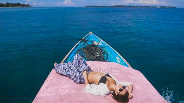 Zblízka se atraktivní model opalováním na palubě malé jachty na otevřeném moři. Mladá dívka oblečená v černých plavkách, modré kalhoty a černé brýle ležet na pódiu lodi a užívat